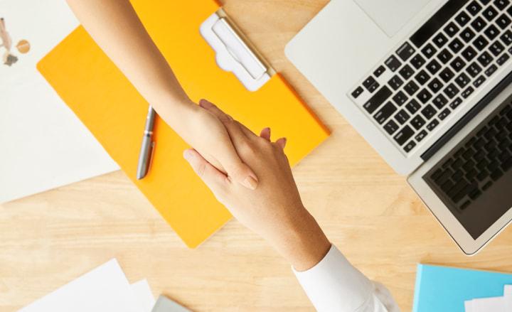 職場で握手する人の手